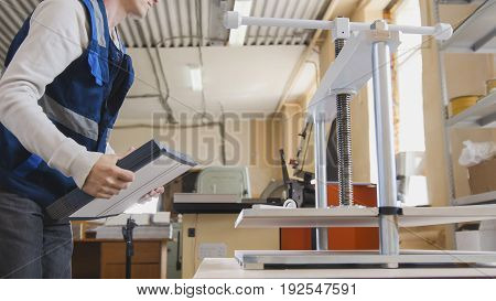 Worker of printing with a stack of paper at the machine, in a printing factory