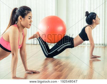 Women Doing Exercise With Fit Ball In Gym Class