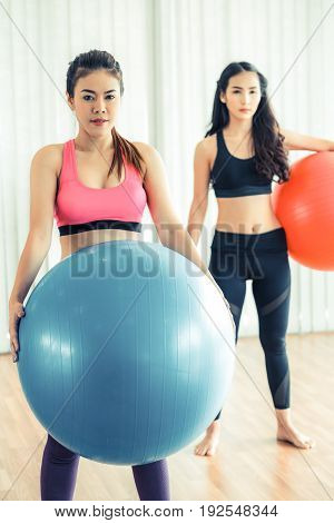 Women Holding Fit Ball In Fitness Gym Group Class