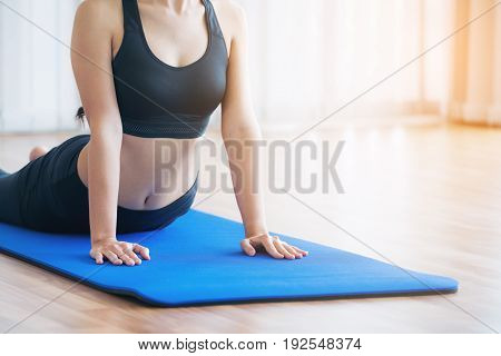 Young Woman Exercising In Indoor Gym On Yoga Mat
