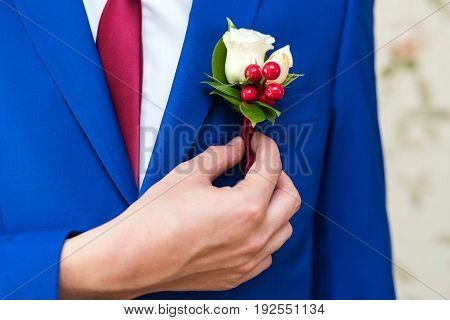 Bridegroom in a blue suit is trying on a boutonniere for a ceremony closeup