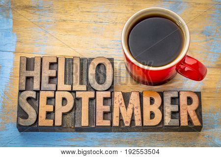 Hello September - word abstract in vintage letterpress wood type blocks against grunge wooden background with a cup of coffee