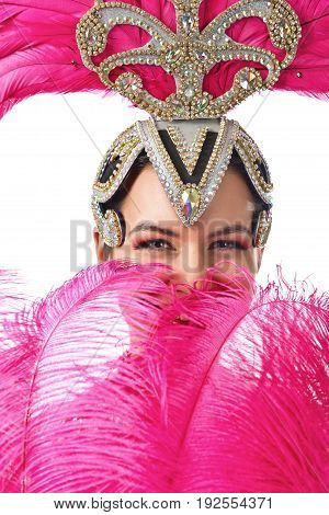 Beautiful woman in cabaret costume with pink feathers and rhinestones.Beautiful professional make-up perfect headdress with natural feathers isolated on white background.
