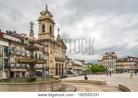 GUIMARAES,PORTUGAL - MAY 14,2017 - Fountain and Basilica Sao Pedro at the sqaure Largo do Toural in Guimaraes. The city Guimaraes was settled in the 9th century at which time it was called Vimaranes.