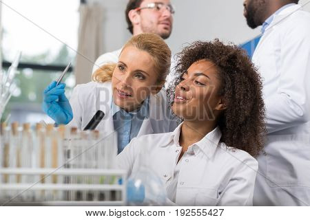 Two Female Scientist Examine Sample Working In Modern Laboratory, Group Of Researchers Making Experiment In Lab