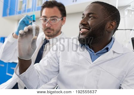 Two Male Laboratory Scientists Examining Samples Injection In Syringe, Mix Race Doctors In Lab Study Results Of Chemical Research Experiment