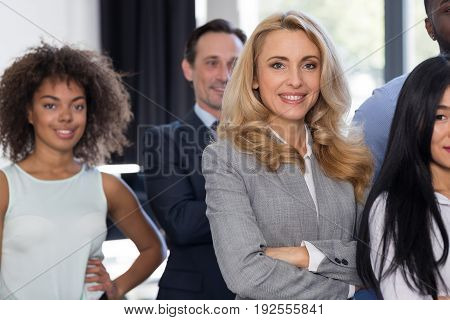 Businesswoman Leading Businesspeople Group In Modern Office Smiling, Female Boss Over Business People Team Stand Folded Hands With Successful Mix Race Colleagues