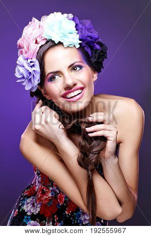 beautiful young woman with purple eye shadow and pink lips. Braided hairstyle with flowers on head. Copy space.
