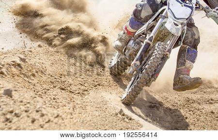 motocross racer accelerating speed in dirt track