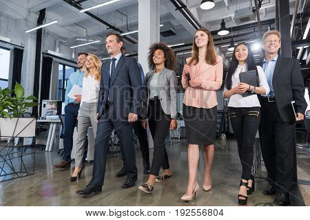 Full Length Business People Team Walking In Modern Office, Confident Businessmen And Businesswomen In Suits Diverse With Mature Leader In Foreground