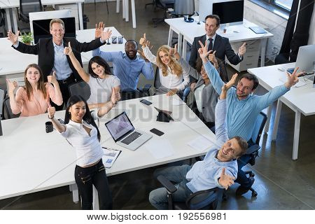 Successful Excited Mix Race Businesspeople Team Sitting At Table On Meeting, Holding Raised Hand Happy Smiling Business Man And Woman Working Together