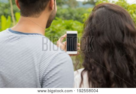 Man And Woman Hold Cell Smart Phone With Empty Screen, Back Rear View Over Green Tropical Rain Forest Landscape