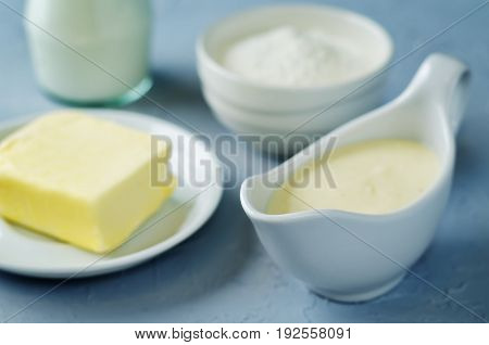 White sauce Bechamel with ingredients on a grey background