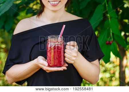 closeup of smiling girl holding glass mason jar of cherry smoothie in her hands. Diet, vegetarian food, healthy lifestyle concept. Woman drinking red berry cocktail outdoor in summer