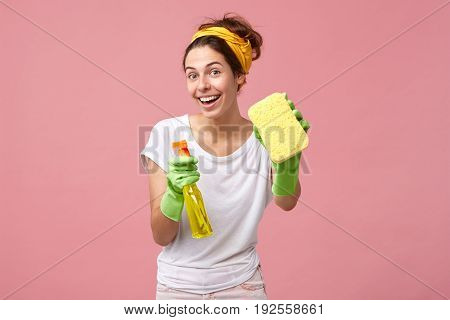 Attractive Positive Young Female In Protective Gloves Ready For Spring Cleaning, Smiling Broadly At