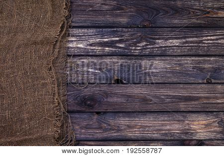 Dark wooden texture with burlap, rustic wood and sack