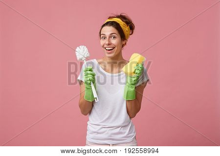 Housework And Housekeeping Concept. Female Cleaner Holding Brush And Mop Having Good Mood Wanting To