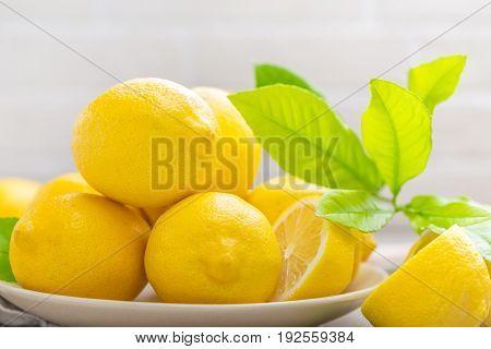 Fresh lemons with lemon leaves close up