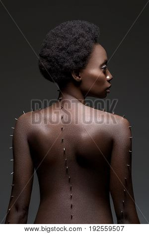 Beautiful naked young black woman with metal pins on body. Profile on black background. Copy space.