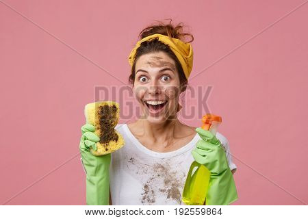 Pretty Maid Cleaner With Happy Surprised Expression Looking With Bugged Eyes Into Camera Showing Dir