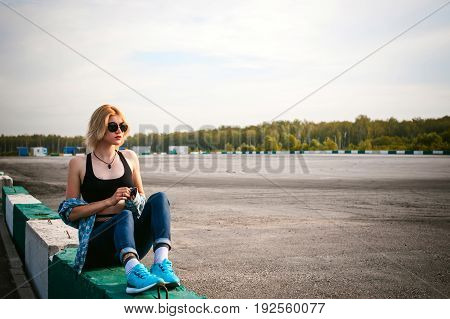 Young Slim Woman Dressed In Blue Checked Shirt Sunglasses, Cap And Jeans, Pantyhose In The Net And T