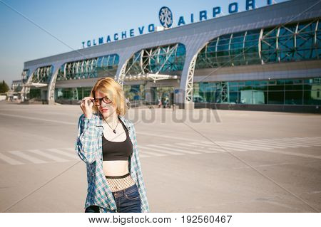 Young Slim Woman Dressed In Blue Checked Shirt, Jeans, Glasses. Will Depart At Dawn On Summer Day On