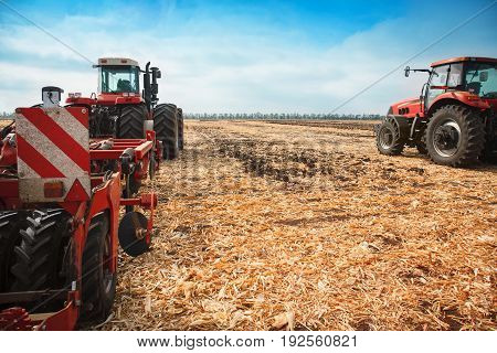 Two tractors with a plow in a field on a sunny day. The concept of work in a fields and agriculture industry.