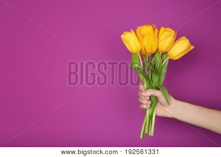 Woman holding beautiful fresh bouquet on lilac color background