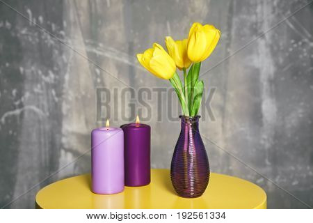 Bouquet of beautiful tulips in vase and lilac color candles on table