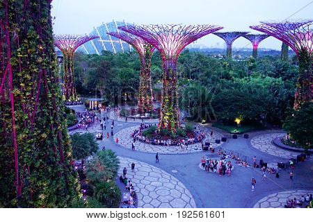 Singapore, Singapore - February 14, 2017: People walk around evening supergrove trees in Gardens By the Bay, situated in Marina Bay area in Singapore, it's a new design garden with innovative.