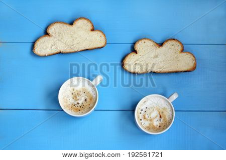 Flat layout with frothy cappuccino in cups and white bread on a blue table / coffee rain in clouds of toast