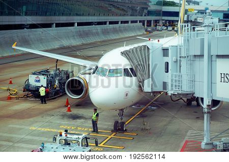 Singapore, Singapore - February 15, 2017: Airfield personal workers check the plane in the Changi Airport of Singapore before boarding.