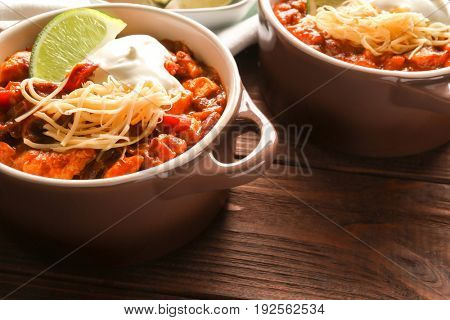 Casserole with delicious chili turkey on wooden table