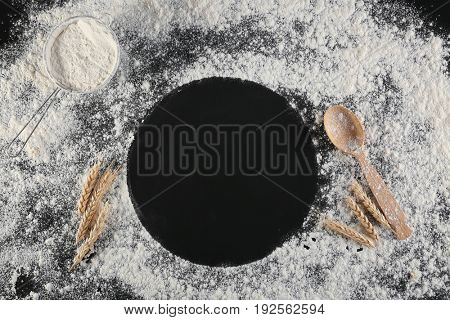 Round frame with scattered flour on dark background