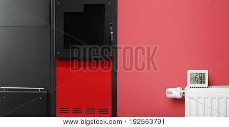 Energy savings concept. Solid fuel boiler and radiator with electronic thermometer on color background