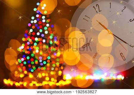 Countdown to holiday celebration. Clock and blurred Christmas tree on background