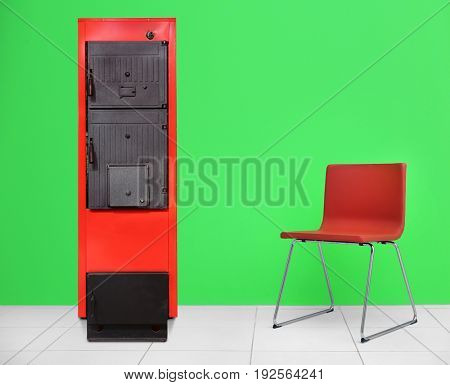 Energy savings concept. Solid fuel boiler and chair on color wall background