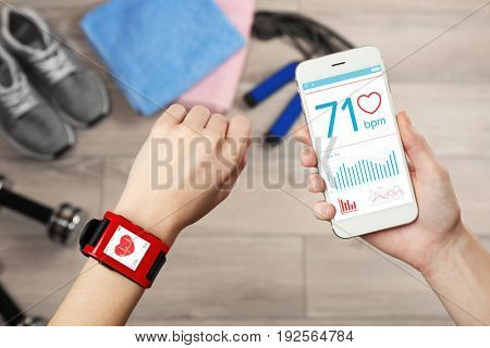 Female hands with heart rate monitor watch and smart phone, closeup
