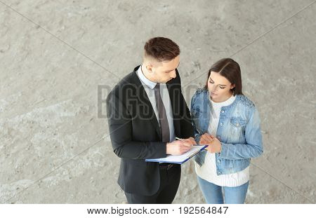 Insurance adjuster and beautiful woman in abandoned building