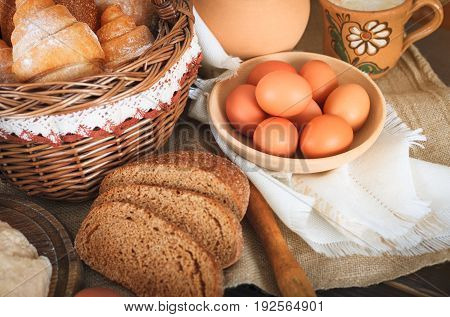 Farm products: eggs milk fresh bread on a wooden table