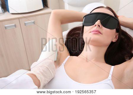 Beautiful woman getting laser epilation in beauty salon