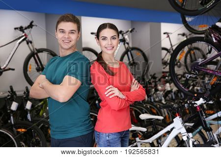 Smiling young woman and man in bicycle shop