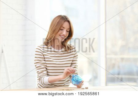 Happy young woman holding piggy bank at desk