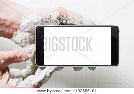 Mobile photography of home repair process. Advertisement or commercial for online building store. Dirty builder hands in plaster with smartphone