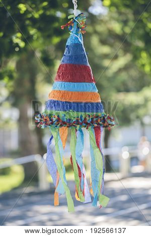 Multi colored cone shaped pinata with focus on foreground