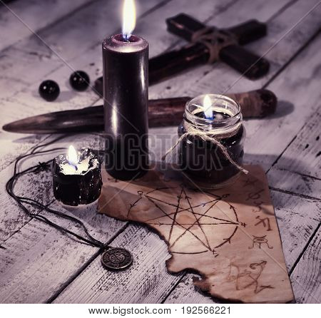 Still life with three black candles, old paper with pentagram and cross. Vampire killer and Halloween concept. Mystic background with occult and magic objects on witch table