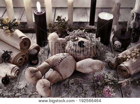 Voodoo doll with black candles and ancient scrolls. Halloween concept. Mystic background with occult and magic objects on witch table