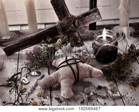 Voodoo doll with cross, herbs and black candle. Halloween concept. Mystic background with occult and magic objects on witch table