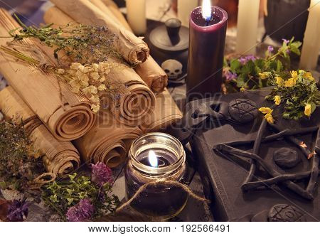 Black candles with old parchments and evil magic book with pentagram on cover. Halloween concept. Mystic background with occult and magic objects on witch ta