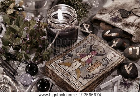 Toned still life with black candle, runes and the tarot cards. Halloween and fortune telling concept. Mystic background with occult and magic objects on witch table
